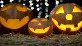 резной : Three halloween pumpkins with eerie faces burning . Black bokeh background. Close up Стоковые видеозаписи