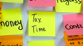 eksi : Sticker with the words tax time on a whiteboard Stok Video