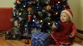 headpiece : Adorable baby girl in red dress and with red headpiece smilling next to a Christmas tree and playing with Christmas globe