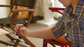 handheld : Female artist draws a pencil sketch drawing on canvas easel in art studio. Student girl learning to draw and paint. Stock Footage
