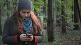 correspondência : girl with stands in the forest in the autumn forest and writes sms