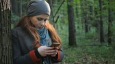 girl with stands in the forest in the autumn forest and writes sms