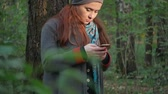 instante : girl with stands in the forest in the autumn forest and writes sms