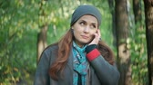 шарф : Attractive hair talking on the phone while standing in the autumn forest Стоковые видеозаписи