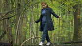 engel : girl in a blue turtleneck and red hair in white sneakers, goes along the log of a fallen tree