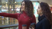 feminine : two beautiful girls with glasses of coffee are standing and chatting in the mall Stock Footage