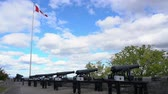 canadense : Cannon and Canada flag swinging with blue sky at Quebec, Canada Stock Footage
