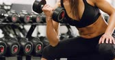 Close-up of well trained woman body lifts weights at fitness gym