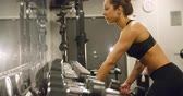 Dedicated woman training and lifting weights in fitness gym