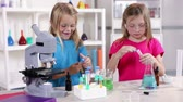 sınıf arkadaşları : Little girls enjoy working with different liquid while learning about chemistry.