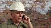 ustabaşı : Man in hardhat with old brick wall in background finishes cell phone conversation then smiles at camera