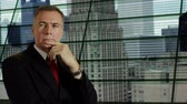 contemplando : A mature handsome businessman with view of high rise office buildings. Stock Footage