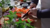 chef kitchen : A chef or cook uses a manual peeling tool to remove the skin from an orange domesticated carrot whose proper name is Daucus Carota. Camera is hand held. Stock Footage