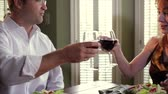 saláta : A happy man and a smiling redheaded woman drinking red wine toast each other while engaging in pleasant conversation. Camera tilts and pans. Stock mozgókép