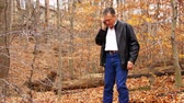 receber : A man walking through a wooded area in autumn stops to take a phone call on his wireless phone.