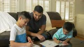 color : Father spending quality time with his sons as the draw and color in workbooks. Stock Footage