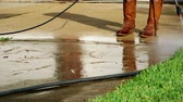 arruela : Safety boots are a must for this person using a pressure washer to clean a dirty residential concrete driveway.