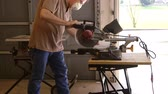 warsztat : A tradesman or handyman homeowner type using a power miter saw to cut a board for a home improvement project. Wideo