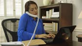 pomocník : A Hispanic woman small business owner CEO multi-tasking using laptop making phone call and taking paperwork from assistant. Dostupné videozáznamy