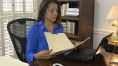 работодатель : Hispanic woman CEO or small business owner sitting in her office is handed a file by an employee.