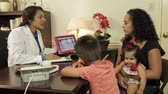 digitální tablet : A Hispanic dentist in her office with a mom and her two children going over dental x-ray image displayed on a tablet pc.