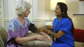 healthcare : A pretty Latin American home health nurse takes blood pressure reading of elderly patient.