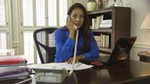 księgowa : A Latin American CEO or small business owner working in her office takes a phone call. Wideo