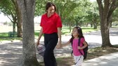 smiling girl : A cheerful single mom walks her cute little girl home after school on beautiful afternoon.