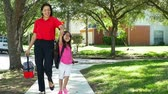 A cheerful single mom walks her cute little girl home after school on beautiful afternoon.