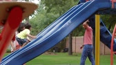 игривый : An energetic four year old boy playing happily climbs up a playground slide while his dad and mom supervise. Стоковые видеозаписи