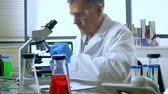 luva : A mature scientist or chemist working in his laboratory using microscope.