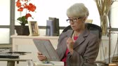 księgowa : An older female attorney or CEO sitting in her office using a tablet pc. Wideo