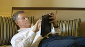 finding : A handsome mature man lying on the couch in his living room using an electronic tablet. Stock Footage