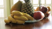 banány : A collection of fruit on a table bathed in lovely sunlight.