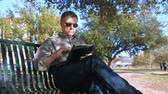 repousante : A handsome mature man relaxing on a park bench shaded by a large tree uses his electronic tablet pc. Vídeos