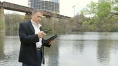 digitální tablet : A mature handsome businessman using an electronic tablet pc takes a cell phone call with a railroad trestle river crossing and a building under construction as his backdrop.