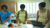 kereviz : Three lovely African American ladies in a kitchen preparing lunch with one using a laptop. Stok Video