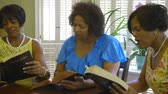biblia : Three lovely African American ladies engage in conversation during Bible study time. Wide shot.
