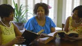 čtenář : Three lovely African American ladies share thoughts during Bible study time.