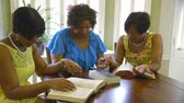 holding : Three lovely African American women hold hands in agreement during prayer after their Bible study time.