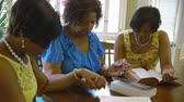 biblia : Three lovely African American women hold hands in prayer during Bible study time.