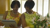 sister : A woman with an electronic tablet pc shows her friend who is working with fresh flowers something of interest. Stock Footage