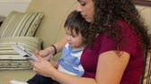 技術 : An adorable little Hispanic toddler is captivated by what his mother is showing him on an electronic tablet.