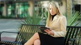 技術 : A pretty blond woman in business attire walks to a park bench then sits down and starts using her electronic or digital tablet.