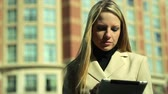 digitální tablet : A pretty blond businesswoman in an urban setting on a bright breezy sunny day uses her digital or electronic tablet.