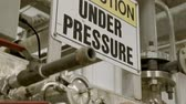 yazılı : camera tilts to an under pressure sign in an industrial area
