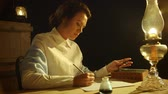 cep : A lovely lady from the early American west in a rustic setting writes a letter by lamp light using a dip pen.