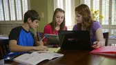 dospívající : Demonstrating teamwork three teenagers using a laptop and digital tablet work together on a homework assignment.