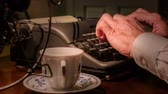 csészealj : A vintage electric fan cools a man sitting in a dimly lit office typing on an old manual typewriter with teacup and saucer close by.