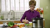 tűzhely : An older woman cutting vegetables to cook in her slow cooker or crock pot. Stock mozgókép